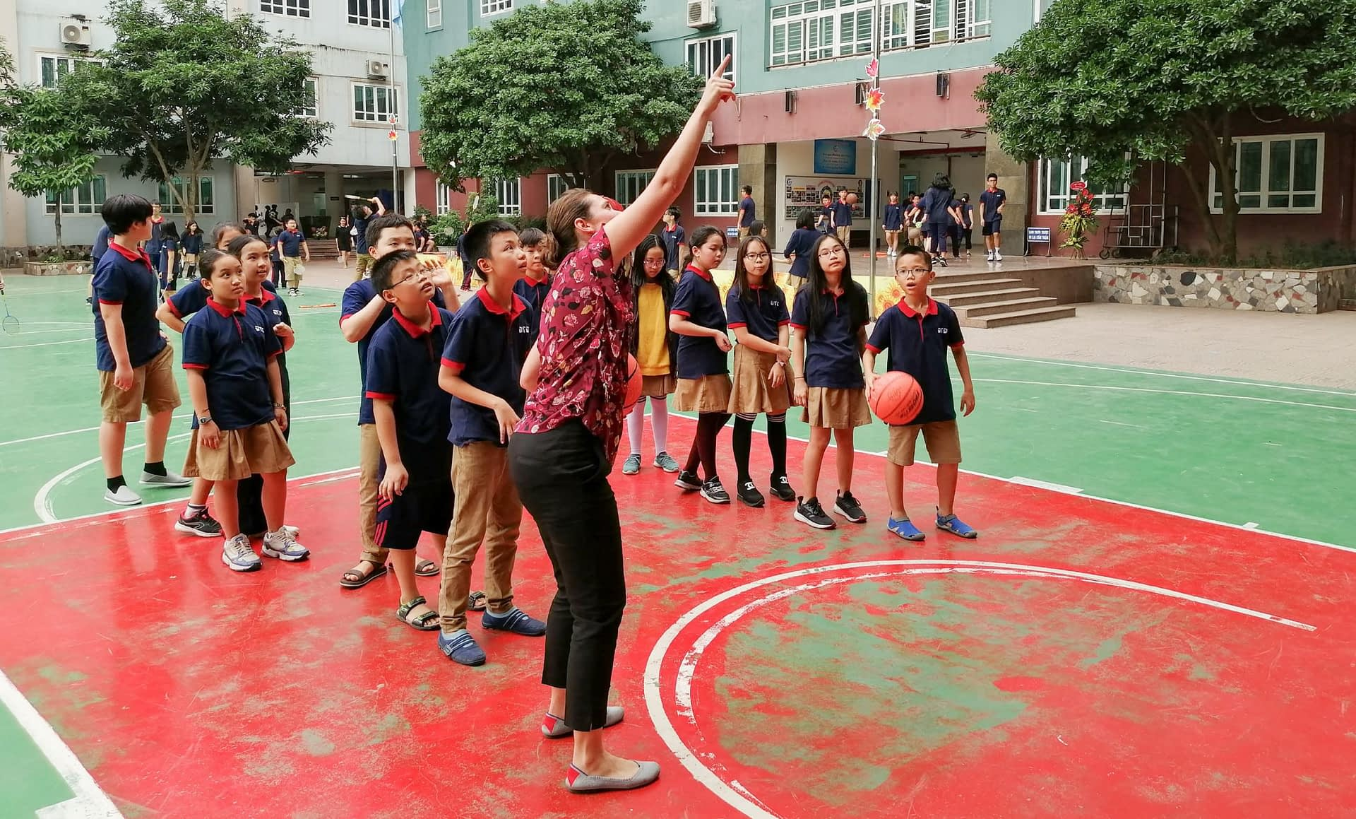 A teacher shows a class how to play basketball